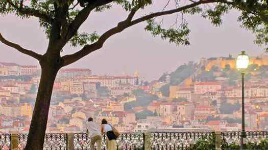 A couple stands while looking at the city of Lisbon