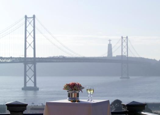 Vista da ponto 25 de abril a partir de um terraço com uma mesa decorada com flores e com um copo de vinho.
